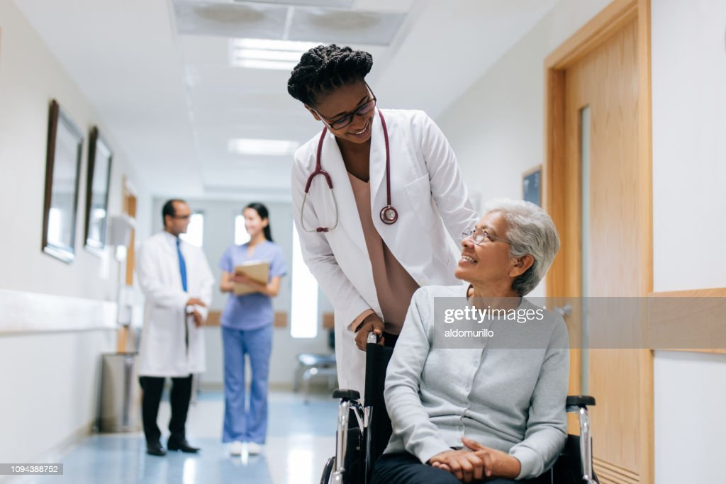Female doctor pushing senior patient on wheelchair : Stock Photo