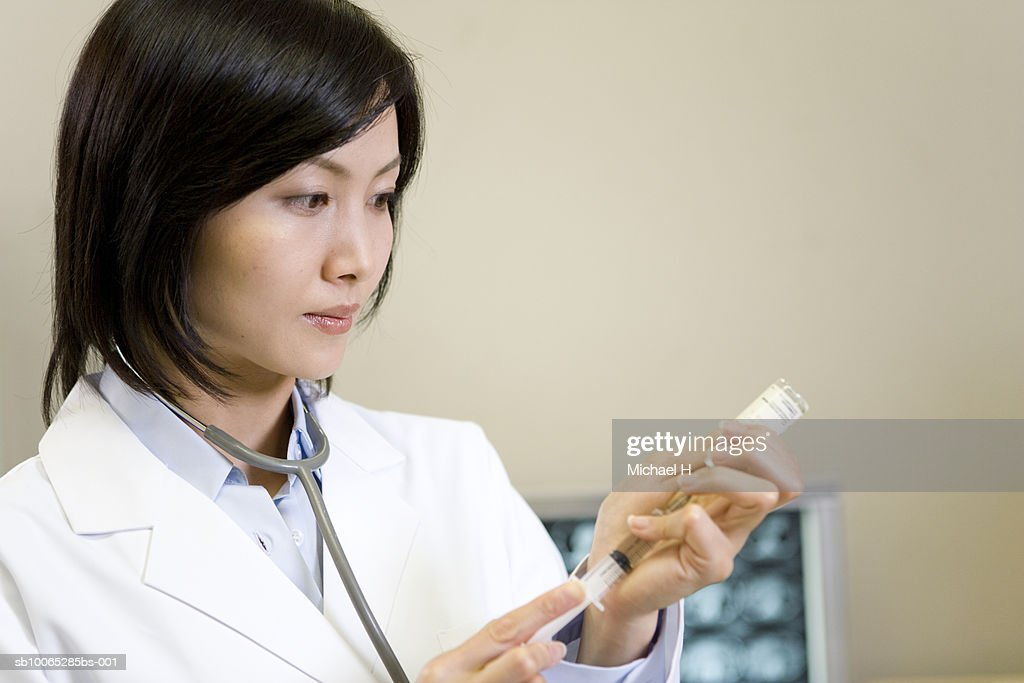 Female doctor putting medicinal solution into syringe, close-up : Foto stock