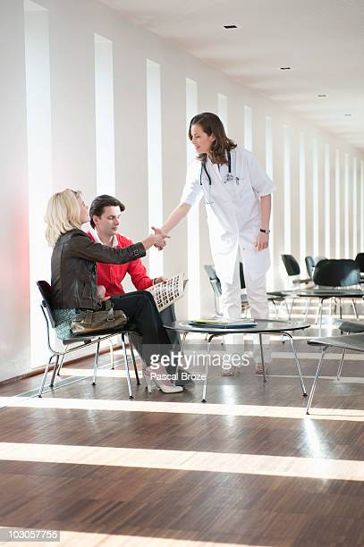 Female doctor shaking hand with a woman