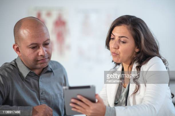 Female Doctor Shares Test Results with Patient Using Digital Tablet
