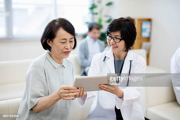 female doctor showing digital tablet to patient in hospital - easy access stock pictures, royalty-free photos & images