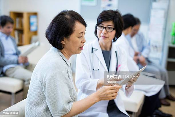female Doctor showing digital tablet to patient in hospital