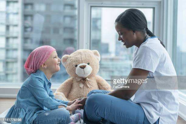 female doctor sits with child patient fighting cancer - oncology stock photos and pictures