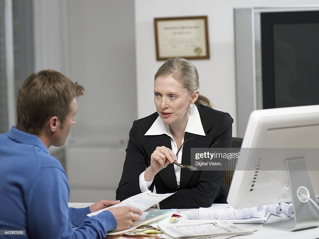 Female Doctor Sitting at Her Desk and Talking to a Male Patient : Stock Photo