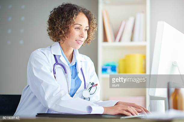 female doctor sitting at her desk - female doctor stock photos and pictures