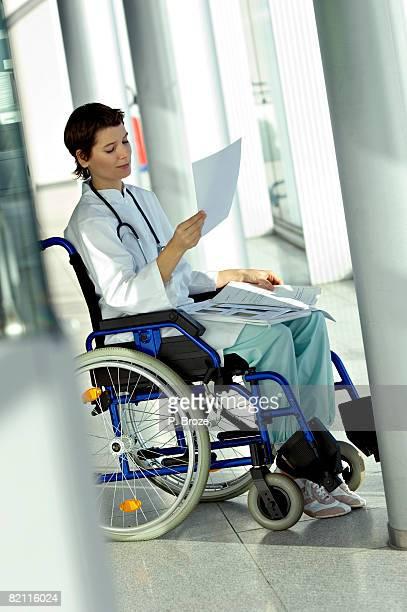 female doctor sitting in a wheelchair and reading a medical record - pessoas com deficiência imagens e fotografias de stock