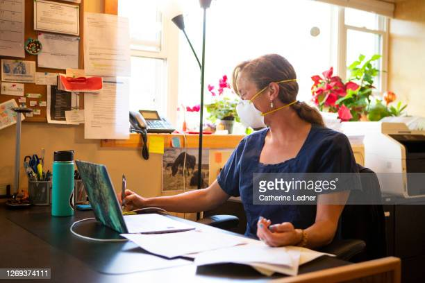female doctor sitting in her office with protective face mask writing a note to herself. - catherine ledner stock pictures, royalty-free photos & images