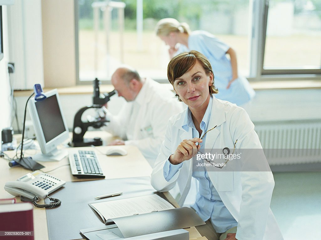 Female doctor sitting in office, portrait : Stock Photo