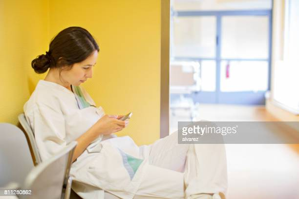 Female doctor sitting in the hospital using mobile phone