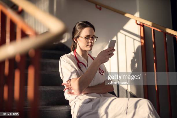 female doctor sitting on stairs with smartphone - dia de las comadres fotografías e imágenes de stock