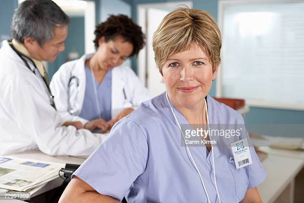 Female doctor smiling, male doctors having discussion in background