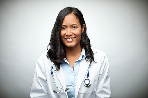Female doctor smiling over white background - gettyimageskorea