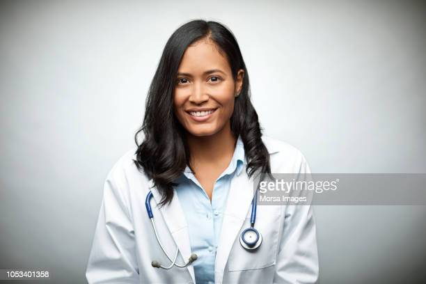 female doctor smiling over white background - laborkittel stock-fotos und bilder