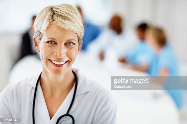 Female doctor smiling with colleagues at the back