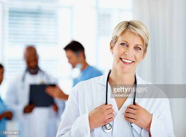 Female doctor smiling with colleagues in the background