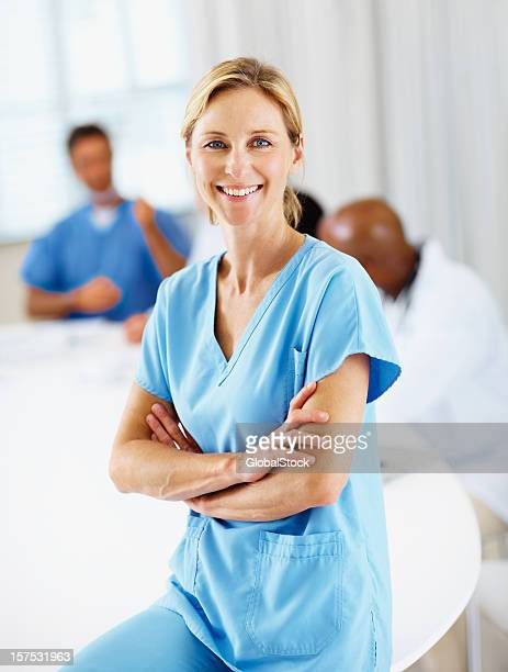 female doctor smiling with colleagues in the background - female nurse stock pictures, royalty-free photos & images