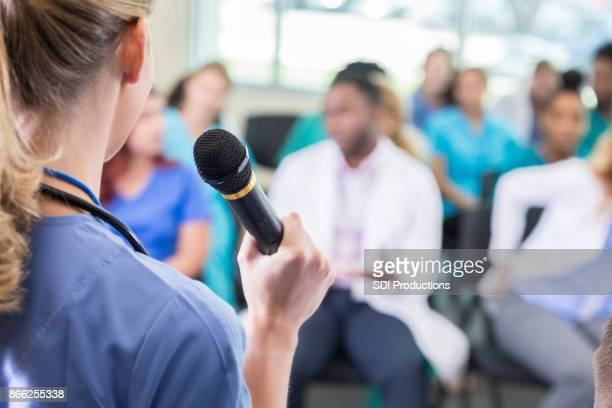 Female doctor speaks to healthcare professionals during continuing education class