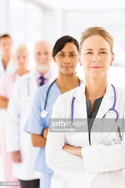 Mulher médico em pé braços cruzados na frente da equipa médica