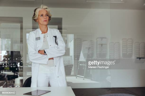 Female doctor standing at table, looking sceptical