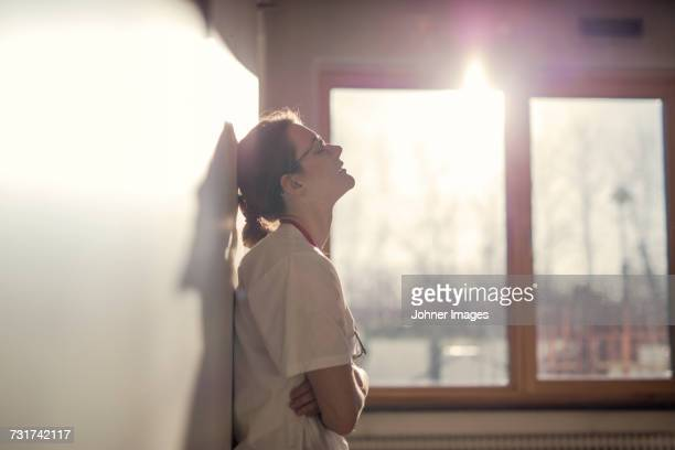 female doctor standing by wall - jet lag stock pictures, royalty-free photos & images