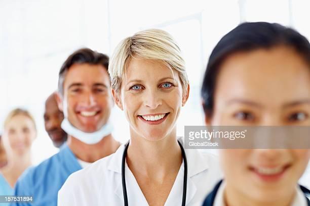 Dottore femminile in piedi con il suo staff e sorridente