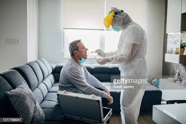 female doctor taking a throat swab test from a senior man at home for covid-19 testing - qtip stock pictures, royalty-free photos & images