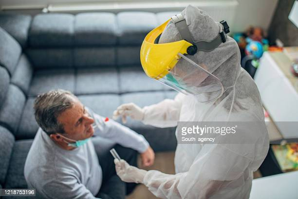 female doctor taking a throat swab test from a senior man at home for covid-19 testing - helmet visor stock pictures, royalty-free photos & images