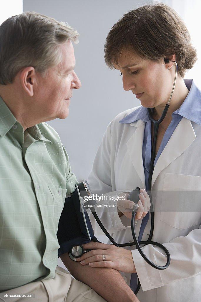 Female doctor taking male patient's blood pressure : Foto de stock