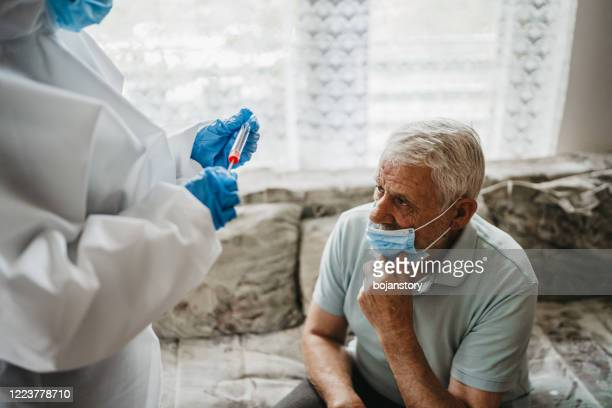 female doctor taking nasal swab test from a senior man at home - nose mask stock pictures, royalty-free photos & images