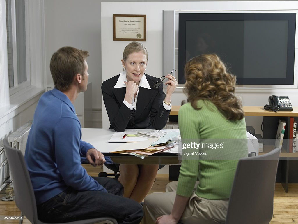 Female Doctor Talking to a Couple Sitting at Her Desk in  Her Clinic : Stock Photo
