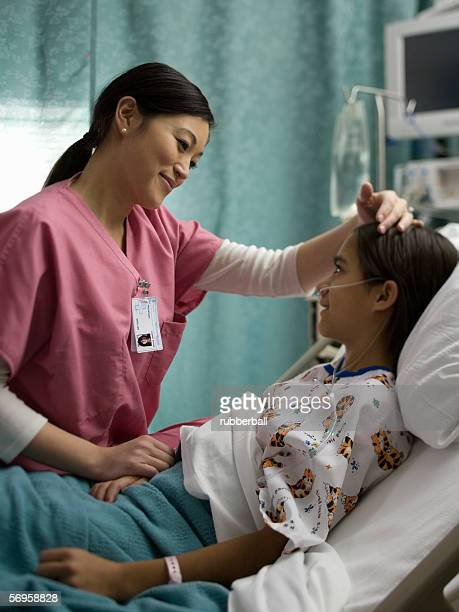 female doctor talking to a patient - girl in hospital bed sick stock photos and pictures