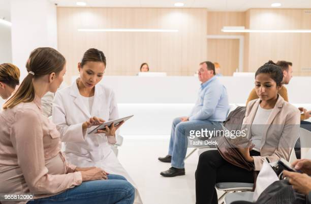 female doctor talking to female patient - waiting room stock pictures, royalty-free photos & images