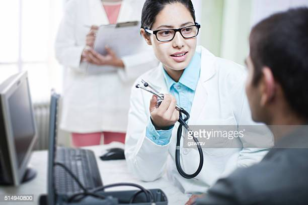 Female doctor talking to male patient by holding stethoscope.