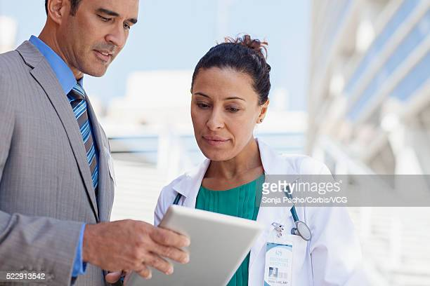 Female doctor talking to man with digital tablet