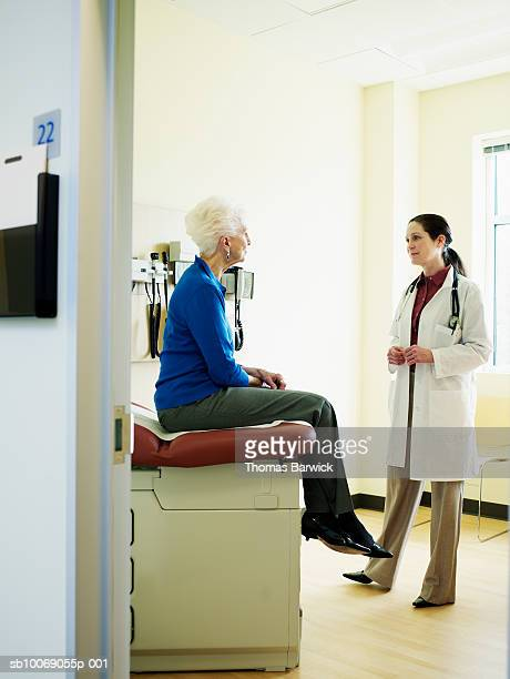 female doctor talking to patient in exam room - examination table stock pictures, royalty-free photos & images