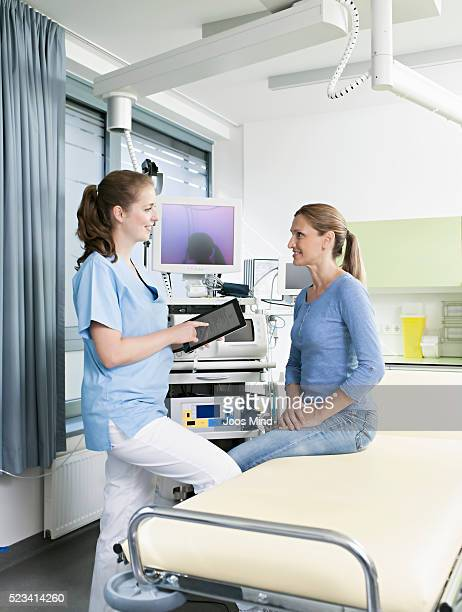 female doctor talking to woman, using digital tablet