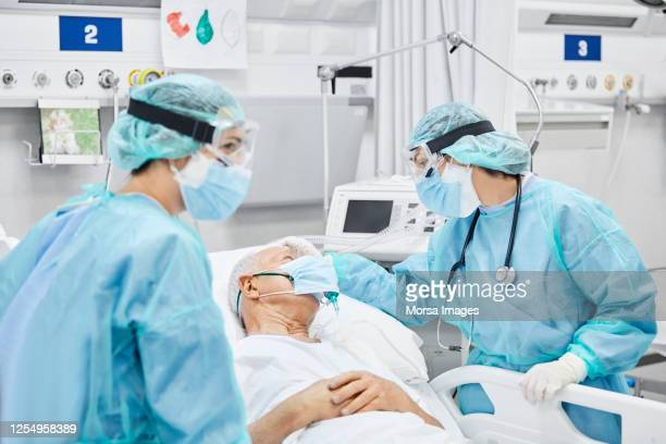 female doctor talking with patient along coworker - hospital stock pictures, royalty-free photos & images