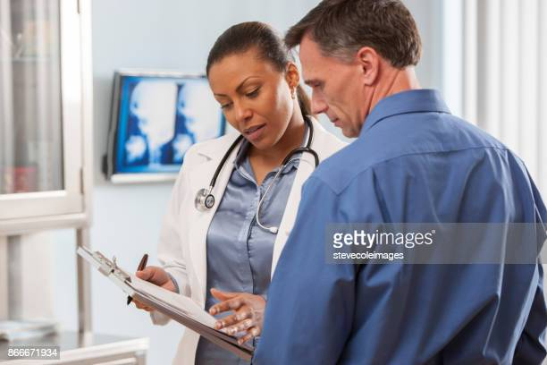 female doctor talking with patient. - male doctor stock photos and pictures