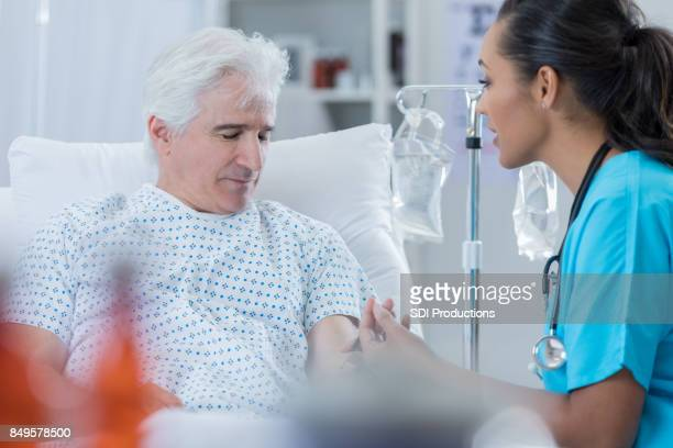 female doctor talks with male patient - iv drip stock pictures, royalty-free photos & images