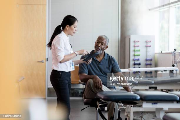 female doctor talks with senior male patient - mid adult stock pictures, royalty-free photos & images