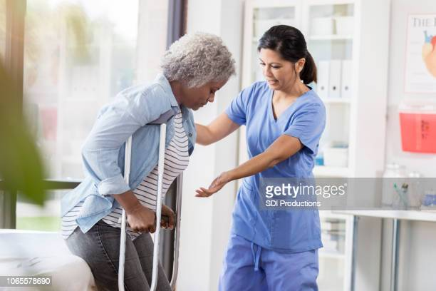 female doctor teaches senior woman to walk with crutches - crutch stock photos and pictures