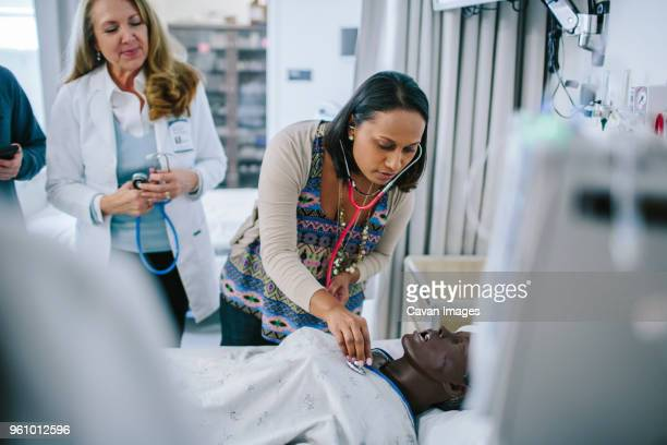 female doctor training coworkers while examining mannequin in medical school - medical student stock pictures, royalty-free photos & images