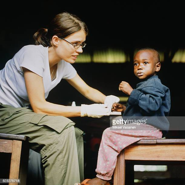 female doctor treating boy in ghana - humanitarian aid stock pictures, royalty-free photos & images