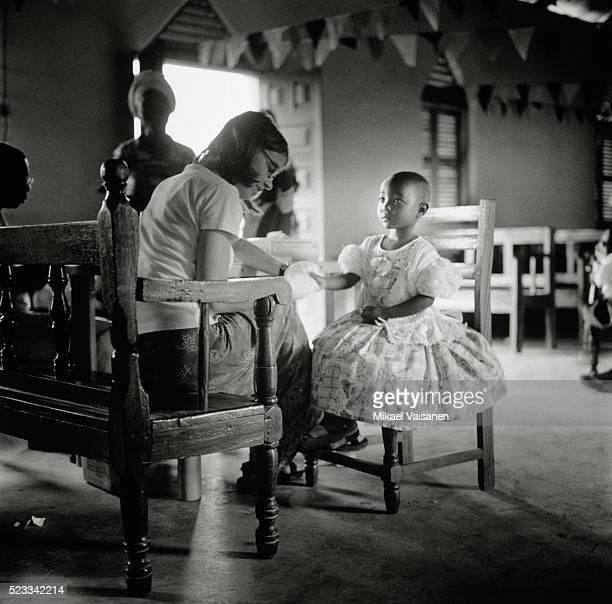 Pediatrician Doctor Examining Ill Boy At Village Stock