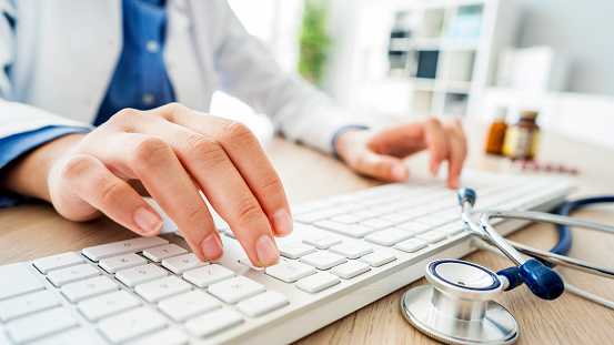 Female doctor typing on computer 1018676898
