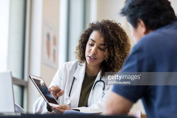 female doctor uses tablet to show x-ray to senior man - doctor stock pictures, royalty-free photos & images