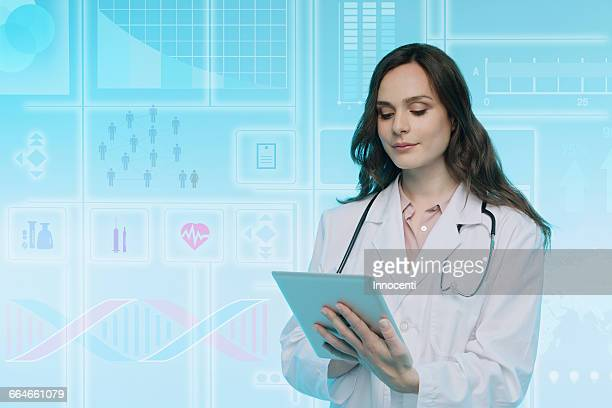 Female doctor using digital tablet, data on graphical screen behind her