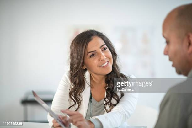 female doctor using digital tablet in consultation - nutritionist stock pictures, royalty-free photos & images