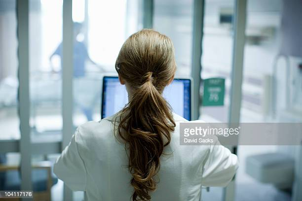 Female doctor using laptop in hospital, rear view