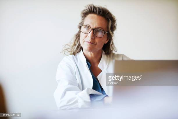 female doctor using laptop - doctor stock pictures, royalty-free photos & images
